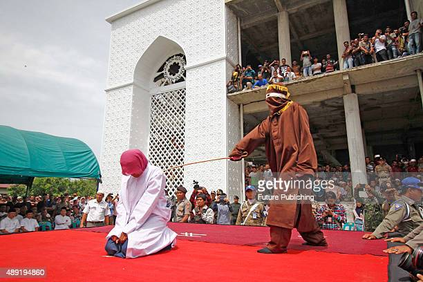 Indonesian Sharia police whips a woman during a public caning ceremony outside a mosque on September 18 2015 in Banda Aceh Indonesia Three women and...