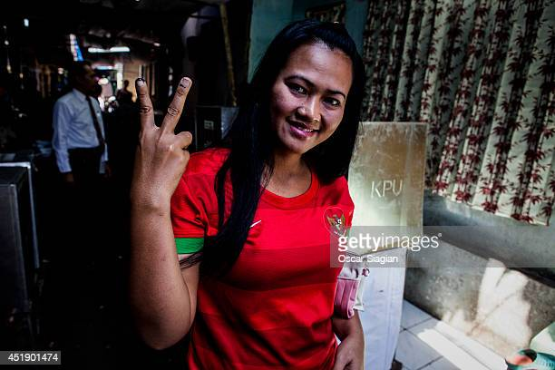 Indonesian shows her inkstained finger after voting at a polling station during the Indonesia presidential election on July 9 2014 in Jakarta...