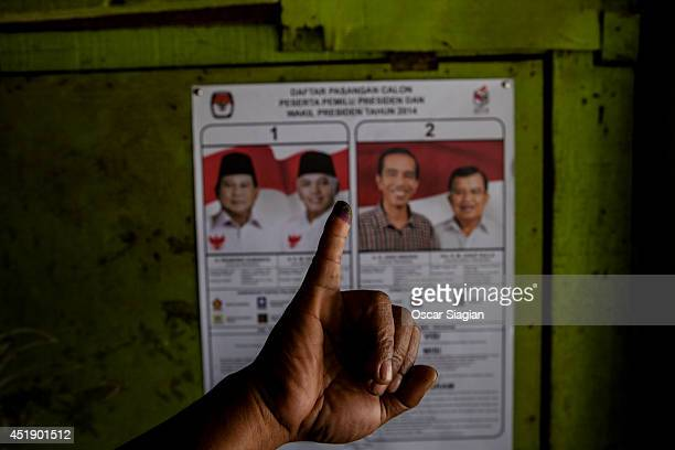 Indonesian shows his inkstained finger after voting at a polling station during the Indonesia presidential election on July 9 2014 in Jakarta...