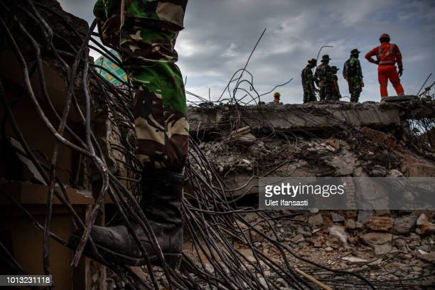 Indonesian soldiers looking for victims trapped at a collapsed mosque following an earthquake in Tanjung on August 8 2018 in Lombok Island Indonesia...