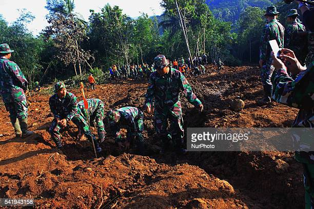 Indonesian soldiers search for victims after a landslide at Caok village on June 21 2016 in Purworejo Central Java Indonesia At least 38 people were...
