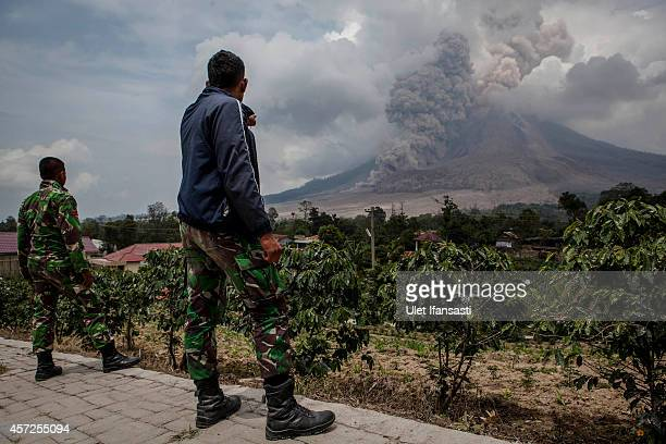 Indonesian soldiers stand guard as Mount Sinabung spews pyroclastic smoke on October 15 2014 in Berastagi Karo district North Sumatra Indonesia Mount...