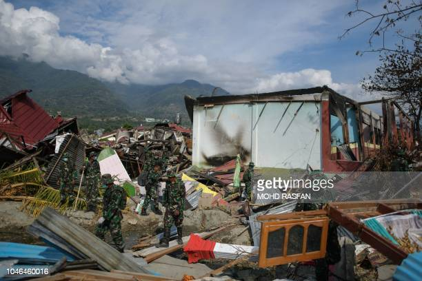 Indonesian soldiers walk through debris at Perumnas Balaroa village in Palu Indonesia's Central Sulawesi on October 6 following the September 28...