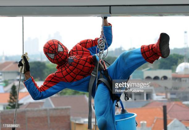 Indonesian 'Spider-Man' window cleaner, 37-year-old Teguh looses his balance before continuing to clean the glass windows of the 18-storey Alana...