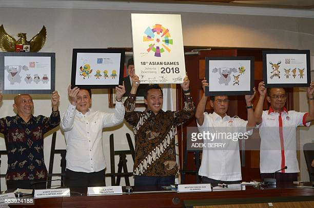 Indonesian Sport and Youth Minister Imam Nachrowi holds up the new logo for the 2018 Asian Games as head of the president's staff Teten Masduki head...