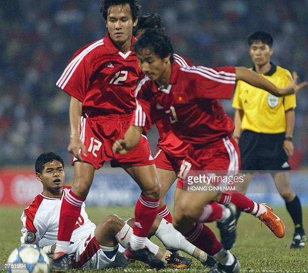 Indonesian striker Bambang Pamungkas loses the ball after dualing with Vietnamese Nguyen Minh Phuong and Le Quoc Vuong during a qualifying match at...