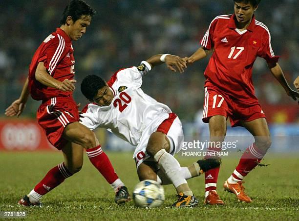 Indonesian striker Bambang Panungkas tries to pass between Vietnamese Vu Duy Hoang and Dang Thanh Phuong during a qualyfying soccer match in the...