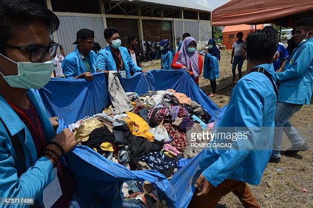 Indonesian student volunteers carry donated clothing for rescued migrants at the confinement area in the fishing port of Kuala Langsa in Aceh...