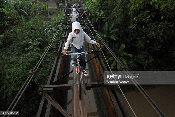 Indonesian students go to school via suspension bridge that connects the Suro village and Plempungan village on March 10 2014 in Boyolali Central...