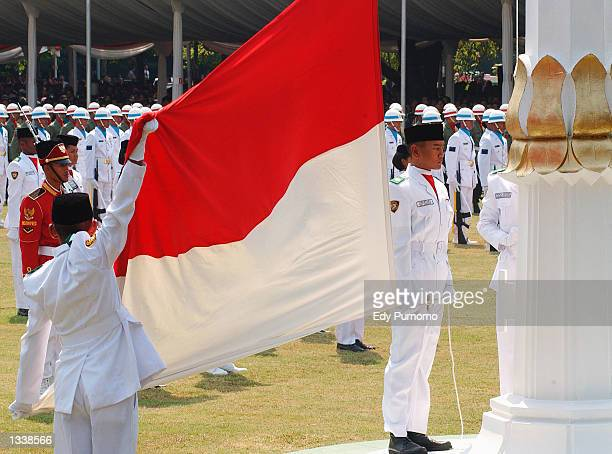 Indonesian students raise the Indonesian flag as part of the celebrations of Indonesia's Independence day on August 17 2002 in the Presidential...