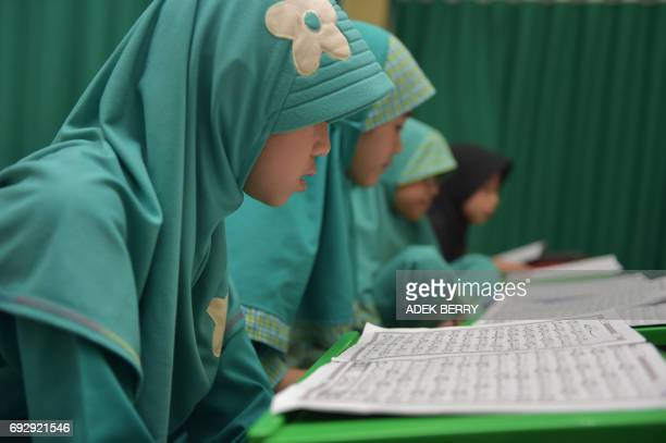 Indonesian students read the Koran at a mosque in Jakarta on June 6, 2017. Muslims throughout the world are marking the month of Ramadan, the holiest...