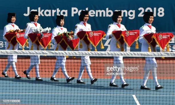 Indonesian students take part in the awards ceremony for the mixed doubles soft tennis event at the 2018 Asian Games in Palembang on August 30 2018