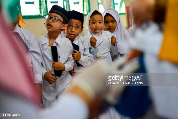 Indonesian students watch as a nurse vaccinates their classmate for diphtheria at a school in Banda Aceh on October 29, 2019.