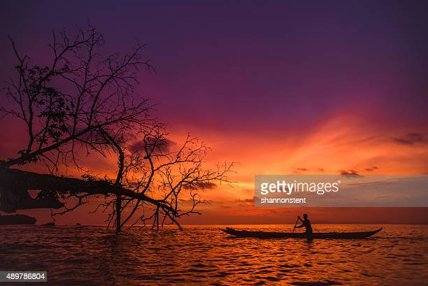 indonesian sunset - dugout canoe stock photos and pictures