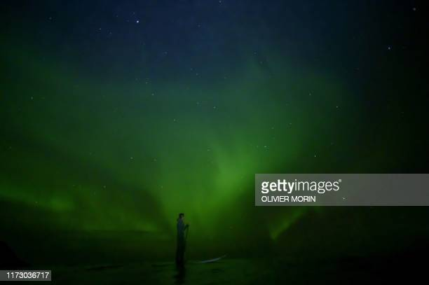 TOPSHOT Indonesian surfer Edi Siswanto rides a StandUp Paddle Board under northern lights in Unstad Lofoten Islands beyond Arctic Circle on September...