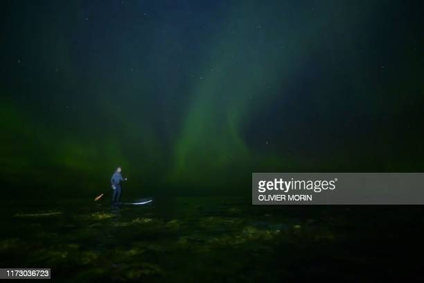 Indonesian surfer Edi Siswanto rides a StandUp Paddle Board under northern lights in Unstad Lofoten Islands beyond Arctic Circle on September 27 2019