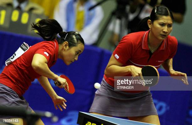 Indonesian table tennis player Ferliana Christine hits a return as her partner Nilasari Ceria looks on during the women's doubles semifinal of the...