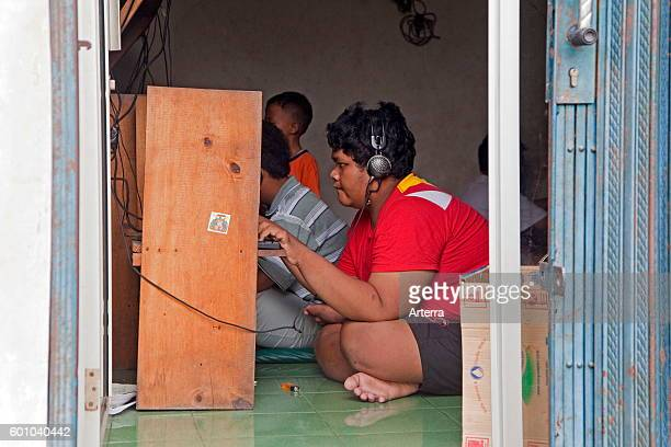 Indonesian teenager surfing in internet cafe / cybercafe in the capital city Jakarta, Java, Indonesia.