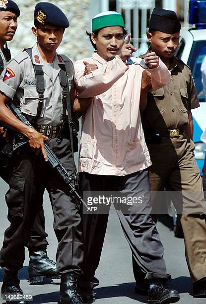 Indonesian terror suspect Abdul Aziz alias Imam Samudra escorted by police shouts to journalists as he leaves the court after his trial in Denpasar...