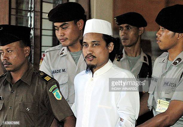 Indonesian terror suspect Abdul Aziz alias Imam Samudra is escorted by police after his trial in Denpasar 28 July 2003 Indonesian prosecutors on...