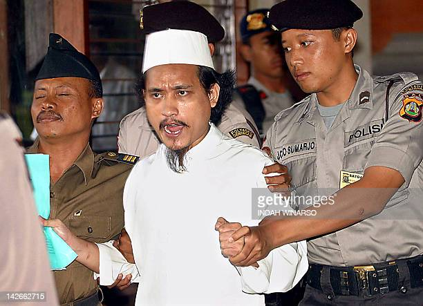 Indonesian terror suspect Abdul Aziz alias Imam Samudra is escorted by police after his trial in Denpasar 11 August 2003 The alleged mastermind of...