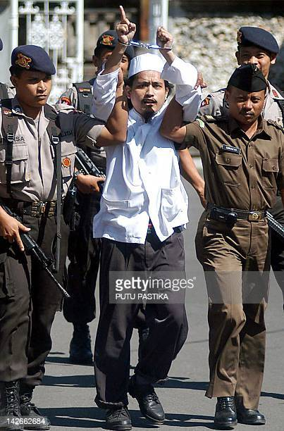 Indonesian terror suspect Abdul Aziz alias Imam Samudra points his finger and shouts 'Allah is great' after his trial in Denpasar 28 July 2003...