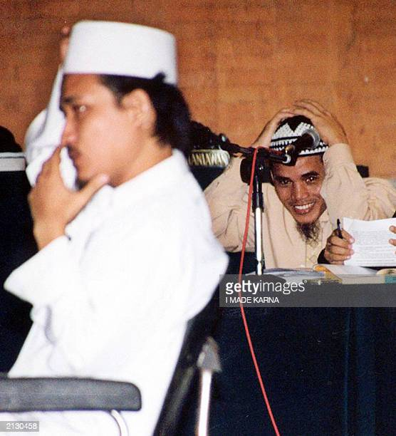 Indonesian terror suspect Amrozi fixes his cap as terror suspect Abdul Aziz alias Imam Samudra testifies for him during a trial in Denpasar Bali 11...
