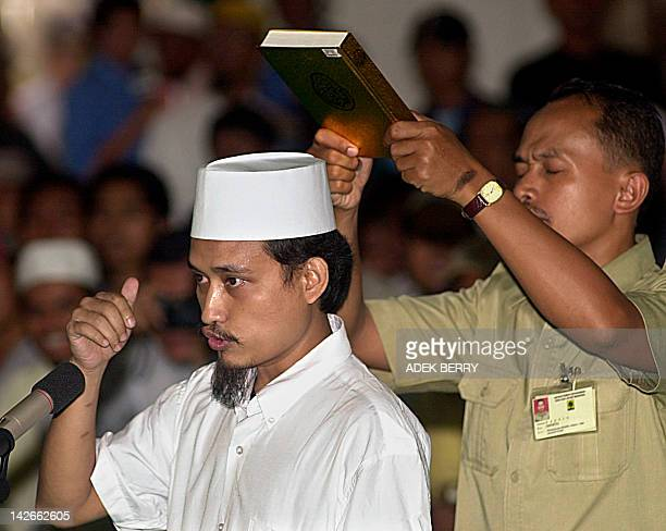 Indonesian terror suspect Imam Samudera alias Abdul Aziz argues with a judges panel as he rejects to taken an oath with the Koran above his head...