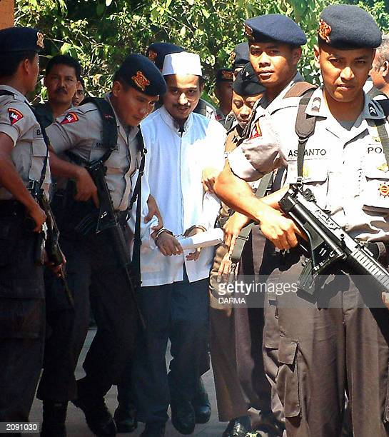 Indonesian terror suspect Imam Samudra alias Abdul Aziz is escorted by police prior his trial at Denpasar court in Denpasar Bali 02 June 2003 Imam...