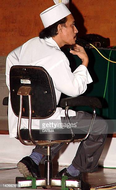 Indonesian terror suspect Imam Samudra alias Abdul Aziz strokes his beard during a trial at Denpasar court in Denpasar Bali 02 June 2003 Imam...
