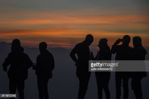 Indonesian tourists wait for members of the Tengger tribe as the sun rises at mount Bromo volcano during the Yadnya Kasada Festival in Probolinggo on...