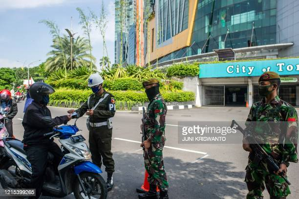 Indonesian troops man a check point as a preventative measure to the COVID-19 coronavirus outbreak in Surabaya, East Java on May 27, 2020