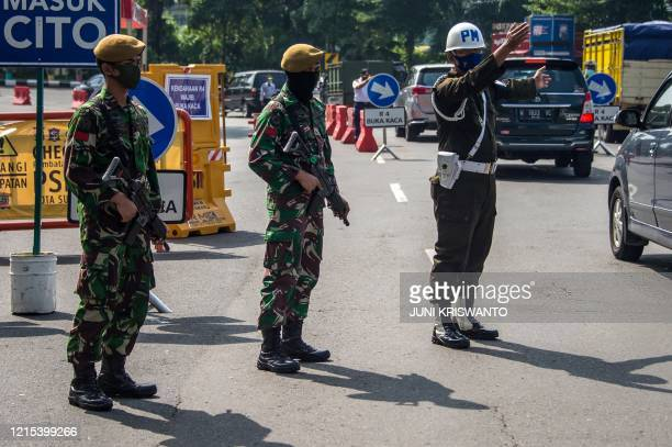 Indonesian troops man a check point as a preventative measure to the COVID-19 coronavirus outbreak in Surabaya, East Java on May 27, 2020.