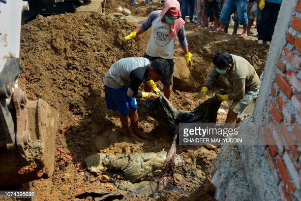 Indonesian villagers carry the remains of the 2004 tsunami and earthquake victims discovered in Kajhu Aceh province on December 19 2018 Remains of...