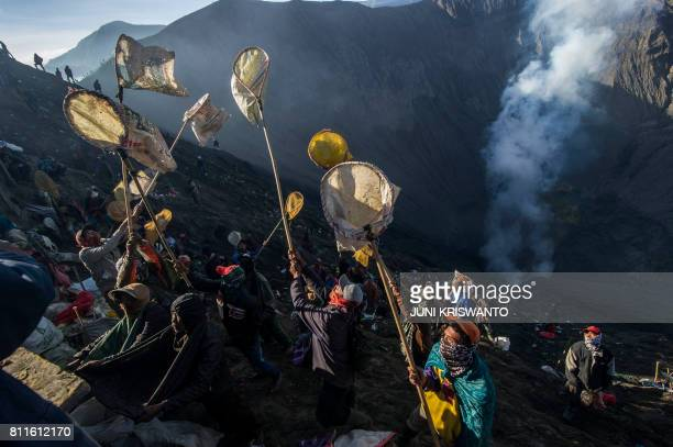 TOPSHOT Indonesian villagers catch money and live offerings thrown by members of the Tengger tribe into the crater of mount Bromo volcano during the...