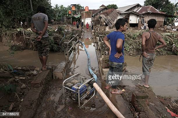 Indonesian villagers look on after waters receded following flash floods in Kamulyan village in Banyumas Central Java on June 19 2016 Flash floods...