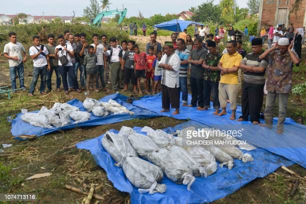 TOPSHOT Indonesian villagers perform funeral prayers on the discovered remains of the 2004 tsunami and earthquake victims in Kajhu Aceh province on...