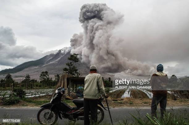 TOPSHOT Indonesian villagers watch an eruption of Mount Sinabung volcano in Karo North Sumatra on November 24 2017 Sinabung roared back to life in...
