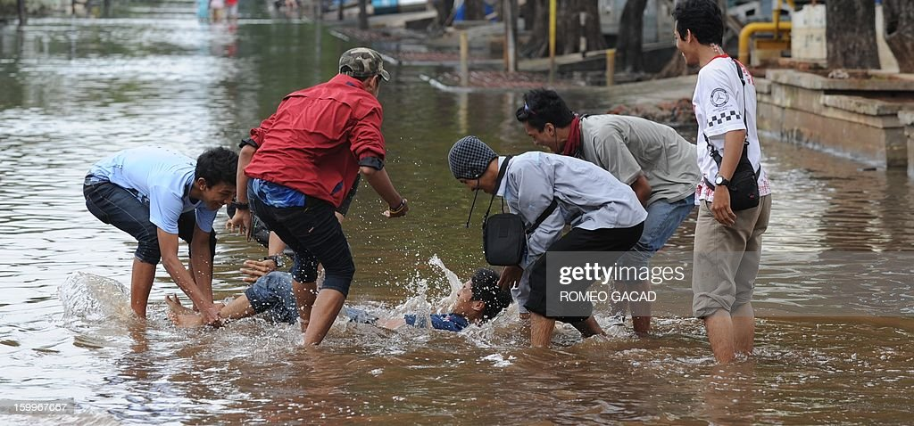 Indonesian volunteers dunk their colleague in the floodwaters after distributing relief goods to flood victims in Jakarta on January 24, 2013. Indonesia's National Disaster Mitigation Agency (BNPB) said more than 30,000 people were displaced while 20 people died during the widespread flooding that hit Jakarta as the weather bureau forecast more rains in the coming days.