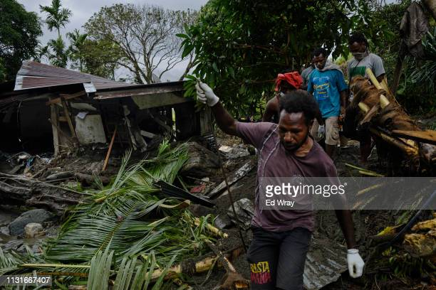 Indonesian volunteers make their way past a flood damaged home as they look for the remains of victims trapped under debris on March 20 2019 in...