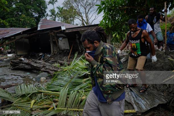 Indonesian volunteers walk past a flood damaged home as they look for the remains of victims trapped under debris on March 20 2019 in Sentani Papua...