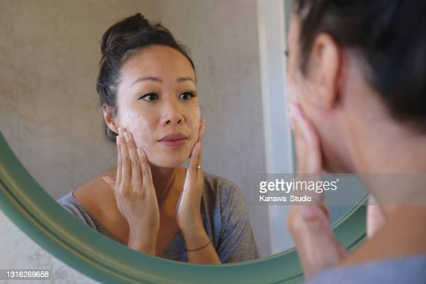 indonesian woman washing her face using beauty cleanser soap - exfoliation stock pictures, royalty-free photos & images