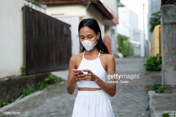 indonesian woman with protection face mask ordering taxi from mobile app - borough district type stock pictures, royalty-free photos & images