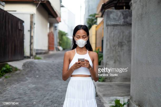 indonesian woman with protection face mask ,using smartphone on residential area - borough district type stock pictures, royalty-free photos & images