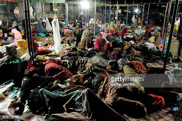 Indonesian women and children displaced by an earthquake rest under a tent in Pidie Jaya Aceh province on December 9 2016 The shallow 65magnitude...