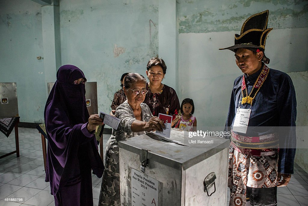 Indonesian women cast their vote at a polling station as an election officer in traditional Kraton soldier known as 'Bergodo' during the Indonesia presidential election on July 9, 2014 in Yogyakarta, Indonesia. Election day in Indonesia sees locals take to the polls to choose between Joko Widodo and Prabowo Subianto as their next president. Recent polls have indicated a tightly fought contest, with allegations of corruption marring the process.