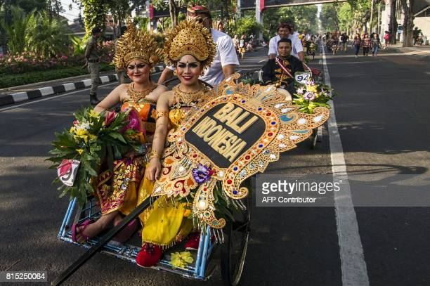 Indonesian women dressed in Balinese traditional outfits ride a becak during a cross culture art festival in Surabaya on July 16 2017 / AFP PHOTO /...