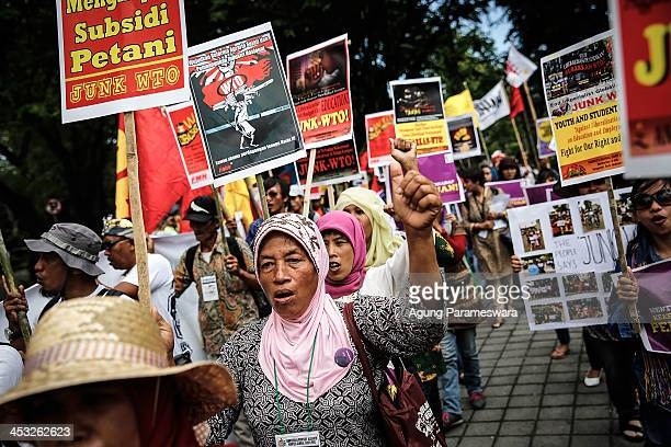 Indonesian women hold posters as they shout slogans during a protest against the World Trade Organization meeting on December 3 2013 in Denpasar...