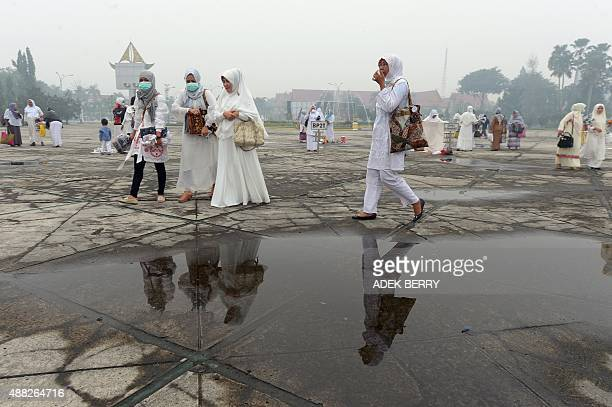 Indonesian women leave after attending prayers in Pekanbaru on September 15 2015 Indonesia on September 14 declared a state of emergency in a...