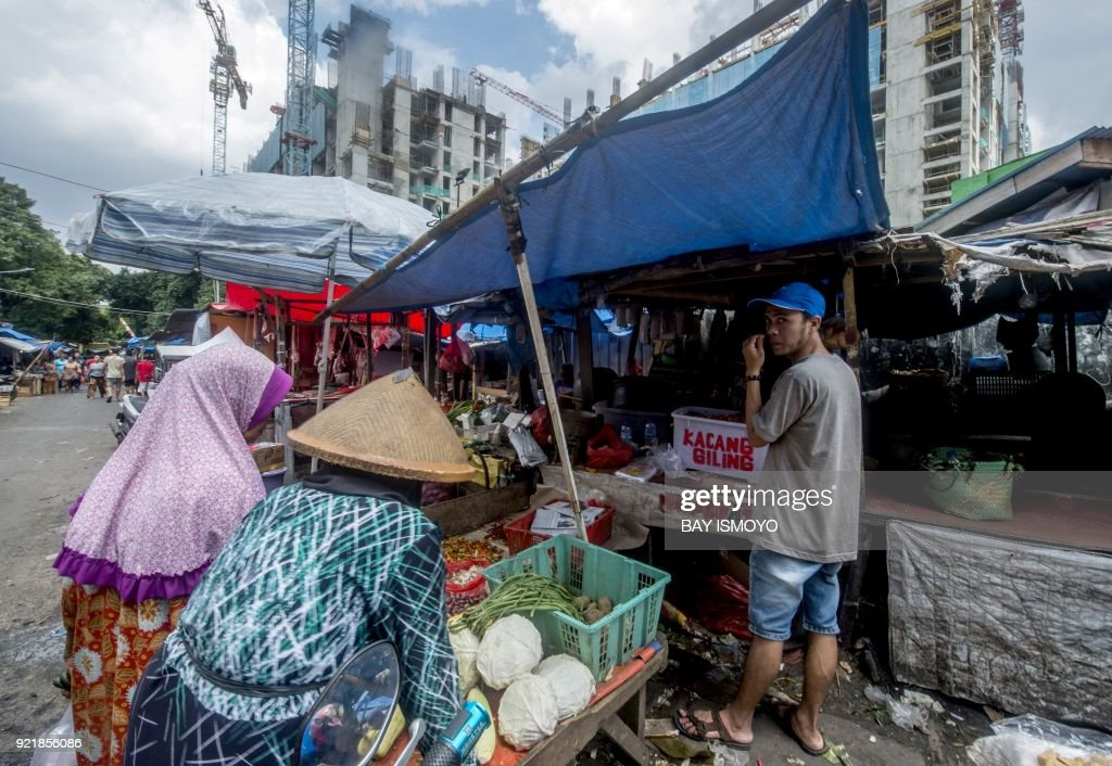 Indonesian women (L) shop for produce at a traditional market in downtown Jakarta on February 21, 2018. /